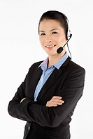 Mid adult businesswoman with headset, arms across chest