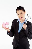 Mid adult businesswoman smashing piggybank with hammer