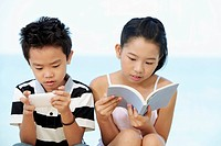 Boy playing game on mobile phone while girl reading book