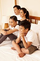 Family watching television together in bed