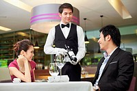 Waiter serving wine to man and woman