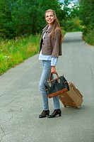 smiling beautiful young woman with road suitcase
