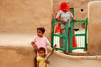 Rajasthani woman with children in hut of gobar or cattle dung looking curiously ; Khuhri ; Jaisalmer ; Rajasthan ; India NO MR