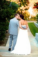 bride & groom stealing a moment alone embraced / kissing after the wedding walking to their bridal suite
