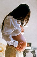 Pregnant woman with long black hair in soft bedroom light