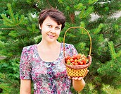 The woman-gardener holds a wattled basket with large and ripe strawberrys