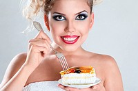 Beautiful blonde woman eating a cake