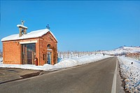Roadside chapel and snowy vineyards. Italy.