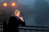 Young woman against a night foggy landscape