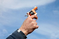 Man's hand firing a starting pistol into the sky