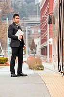 A young businessman walking near a train.