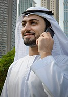 A middle eastern business man stands in front of a building dressed in typical arabic clothing . He is holding a telephone or smartphone to his ear an...