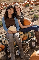Girls sitting in wagon in pumpkin patch