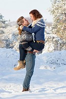 Caucasian couple hugging in snow