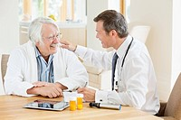 Doctor talking to older patient at house call