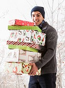 Hispanic man holding Christmas gifts in snow