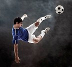 Hispanic soccer player kicking ball in mid air