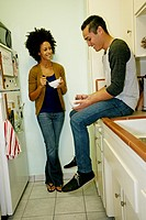 Mixed race couple relaxing in kitchen