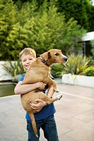 Smiling boy holding dog outdoors