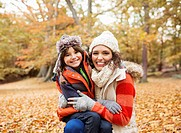 Mother and daughter smiling in autumn leaves
