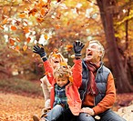 Older couple playing with grandson in autumn leaves