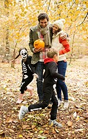 Couple with children in skeleton costumes in park