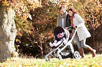 Couple pushing baby in stroller in park