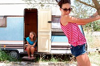 Women relaxing around trailer