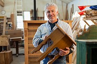 Hispanic craftsman smiling in studio