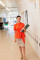 Mixed race teacher holding clipboard in school hallway