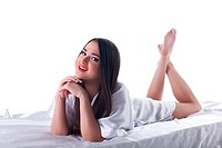 Pretty brunette woman with long hair lying on bed