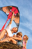 The family outdoors flying kite in the sky
