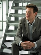 Businessman sitting on steps in office