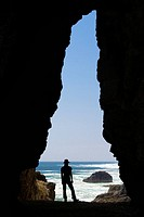 Silhouette of a woman standing at the mouth of a cave on the coast of Arica, Chile, South America