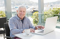 Older man using laptop in cafe
