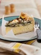 A Slice of Spinach and Goat Cheese Quiche on a Blue Plate
