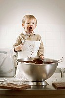 Boy licking whisk in kitchen