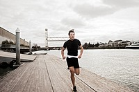 Man running on urban waterfront