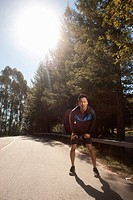 Runner stretching on rural road