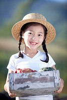 a girl holding a box of harvested vegetables