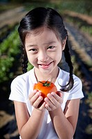 a girl holding a tomato in a farm