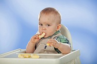 Boy sitting in baby chair, eating corn crisps.