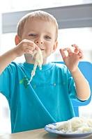 Six year old boy eating sauerkraut.