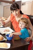 Pregnant woman and her son eating breakfast together.