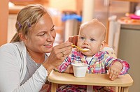 Mother feeding her little daughter.