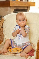 Adorable baby girl sitting in wicker armchair, eating cookies.