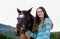 USA, Texas, Teenage girl standing with Quarterhorse, smiling, portrait