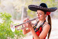 USA, Texas, Young woman playing trumpet