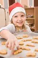 Germany, Girl baking cookies, smiling, portrait