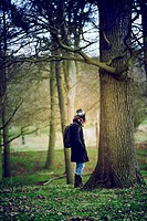Young woman staring at the light in Richmond Park wood, London, UK